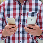 Man holding two smartphones one in each hand